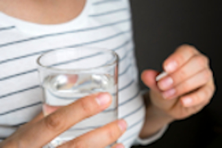 Woman holding a pill and a glass