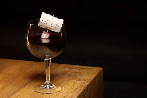 """Help"" Written on a note floating in a wine glass"